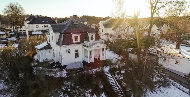 Hovedhuset har nedgang til stor plen med busker og trær.