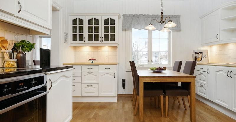 Lyst og praktisk kjøkken med spiseplass.