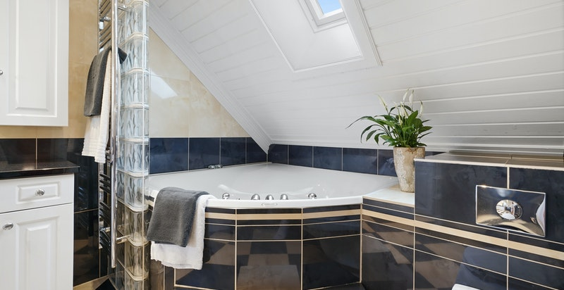 Badet har både stort badekar og dusj
