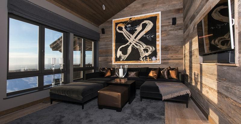 Lekkert innredet stue med med god takhøyde og store vindusflater som gir luft og lys