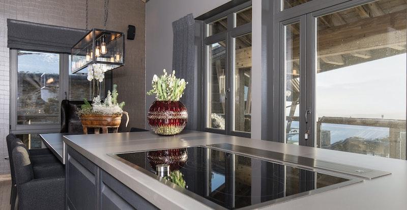 Kjøkkenøy med stenplate som går over i nedsenket integrert spisebord