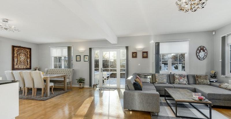 Lys og romslig stue med god plass til flere salonger. Utgang til terrasse og hage.