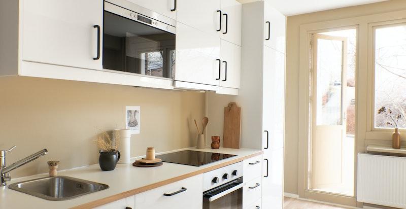Lekkert kjøkken i åpen løsning mot stuen. Innredningen fra Ikea består av lyse fronter og heltre eik benkeplate, nedfelt kum i rustfritt stål.