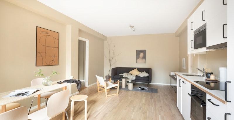 Romslig stue med plass til både sofagruppe og langbord, uten at det legger en demper på den gode romfølelsen.