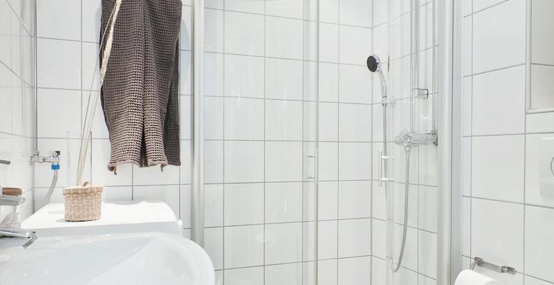 Flislagt bad i god størrelse med dusj med innfellbare dusjdører, toalett og servant. Det er tilrettelagt for både vaskemaskin og tørketrommel.