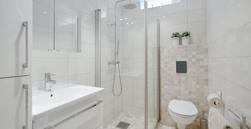 Bad 1 i 1.etg. innredet med servantskap, vegghengt toalett og dusj med innfellbare glassdører
