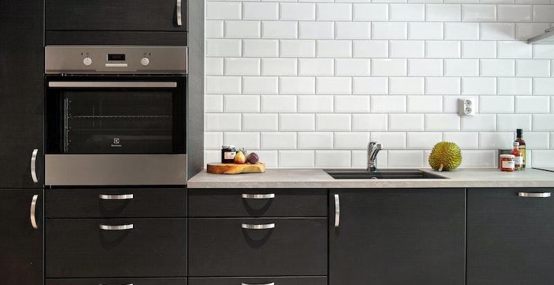 Moderne kjøkkeninnredning med integrerte hvitevarer.