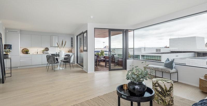 Stuen har storslåtte vindusflater mot vest som gir naturlig lys til rommet og skyvedør ut til balkongen.