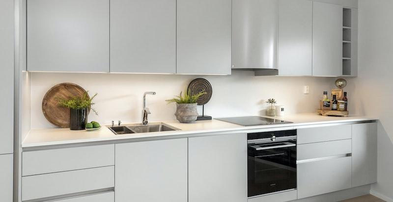 Innredningen er kombinert med hvit trend laminat benkeplate med underlimt vask, hvilket gir kjøkkenet et rent uttrykk.