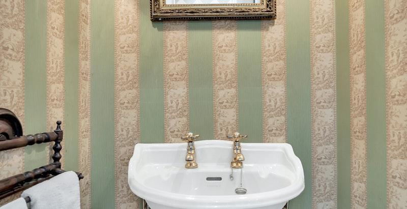 Servantrom/wc med gulv belagt med hvite marmorfliser, tapetserte vegger