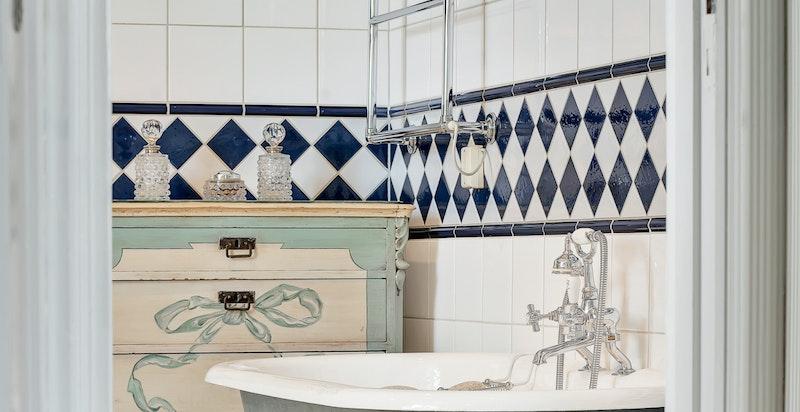 Frittstående badekar med løveføtter, bidé og gulvmontert wc. Egen dusjnisje med glassdør