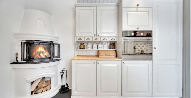 Fliser på benk rundt kokesone samt på vegg over oppvaskkum og kokesone