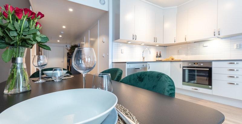 Kjøkken og oppholdssone med plass til spisebord.