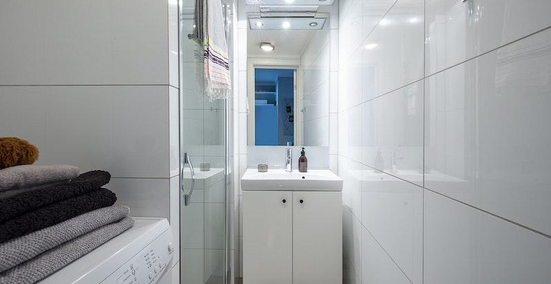 Flislagt bad oppvarmet med varmekabler i gulv. Inneholder servant, dusjhjørne og opplegg til vaskemaskin/tørketrommel.