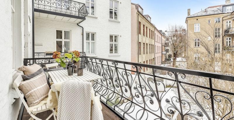 Hyggelig balkong som vender ut mot grønn og rolig bakgård