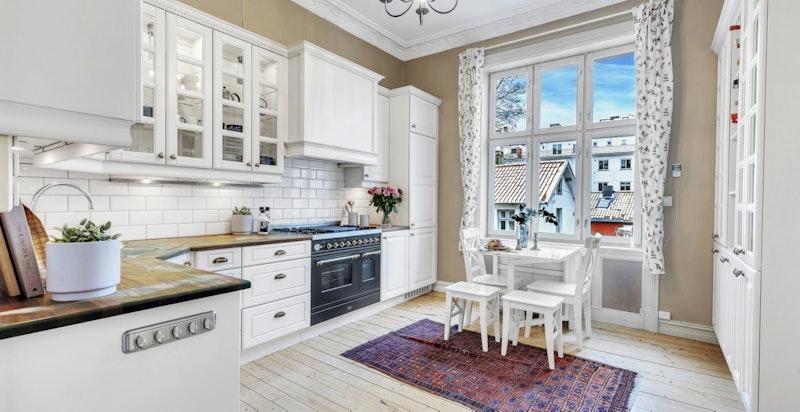 Kjøkkeninnredning med hvite profilerte fronter på skuffer og skapdører. Overskap i samme utførelse, med og uten glass.