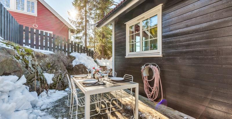 Terrasse på baksiden av huset med adkomst fra kjøkken. Tomten strekker seg et godt stykke opp fra gjerdet