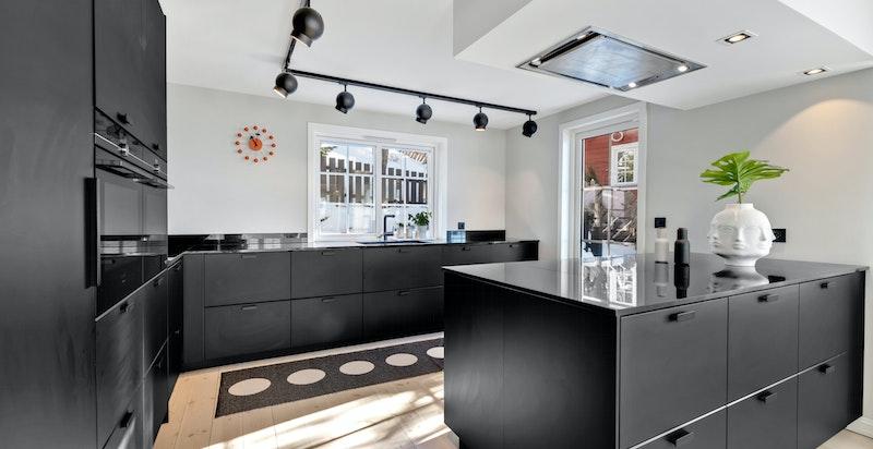 Kjøkkeninnredning fra 2018 med glatte fronter med håndtak. Granitt benkeplater