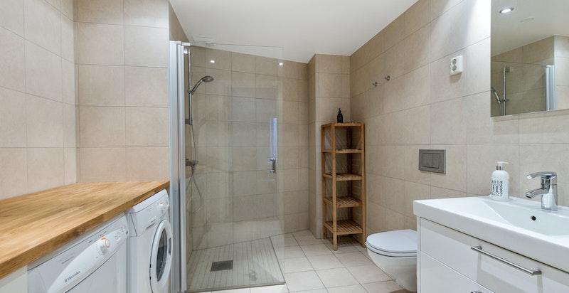 Stort flislagt bad med dusj og vaskemaskin og tørketrommel
