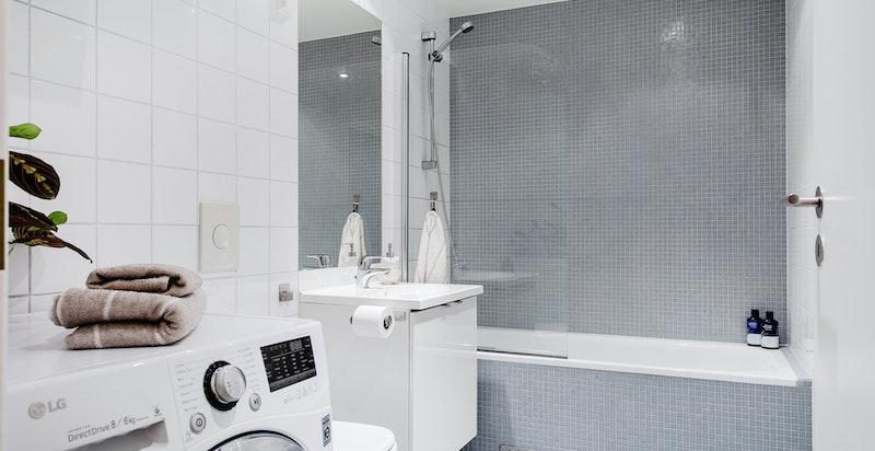 Lekkert bad med oppdaterte fliser og plass for vaskemaskin og tørketrommel