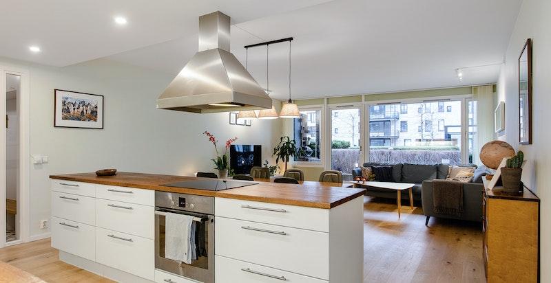 Kjøkken med åpen løsning og stor praktisk kjøkkenøy