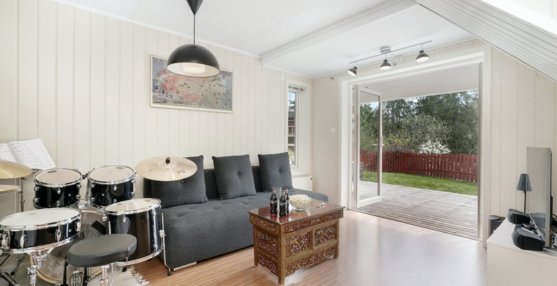 Hyggelig TV-stue med dører du kan åpne helt opp mot hagen