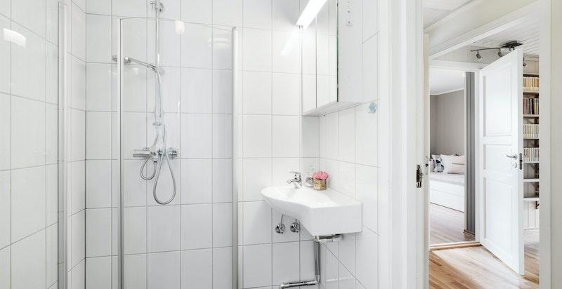 Badet i 1.etg. er innredet med dusj, servantskap og toalett. Flislagt gulv  med varmekabler og flislagte vegger. .