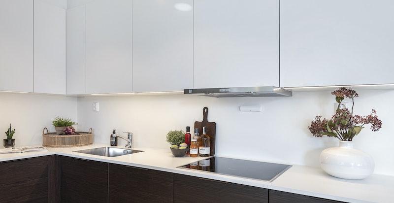Kjøkkenet er praktisk designet med god benke- og oppbevaringsplass.