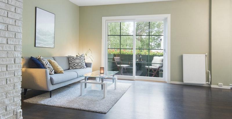 Romslig stue med hjørnekamin og utgang til balkong