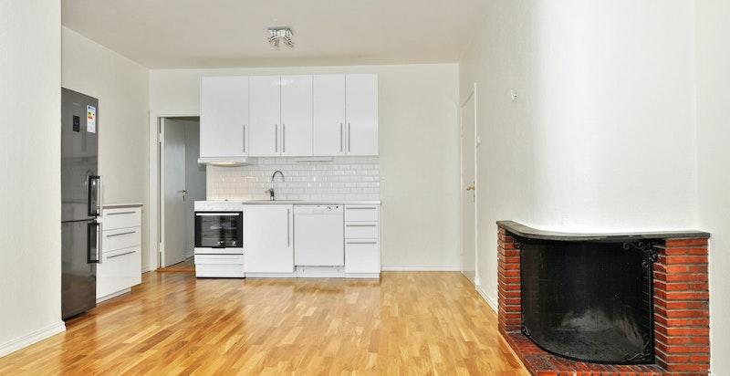 Stue med hyggelig peis og åpen kjøkkenløsning