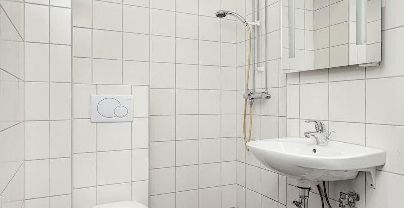 Badet er utstyrt med servant, ettgreps blandebatteri, speil over servant med integrert belysning, veggplassert toalett og dusj.