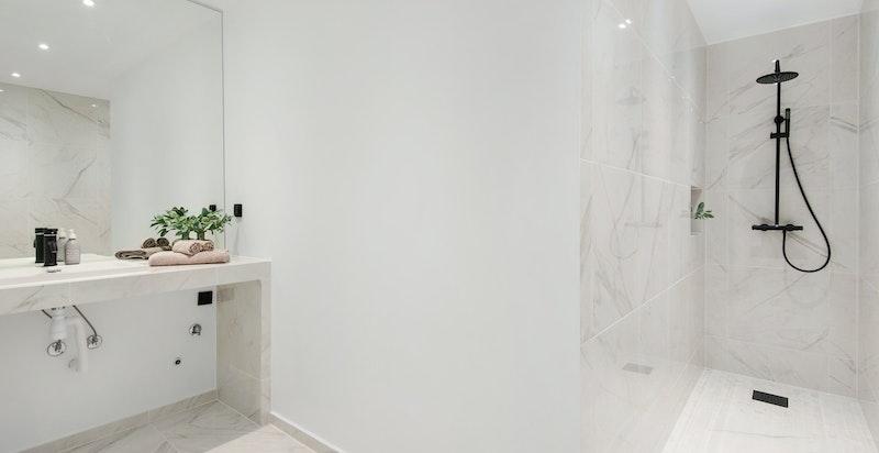 Stort og delikat badeværelse med marmorfliser og opplegg for vaskemaskin under benk.