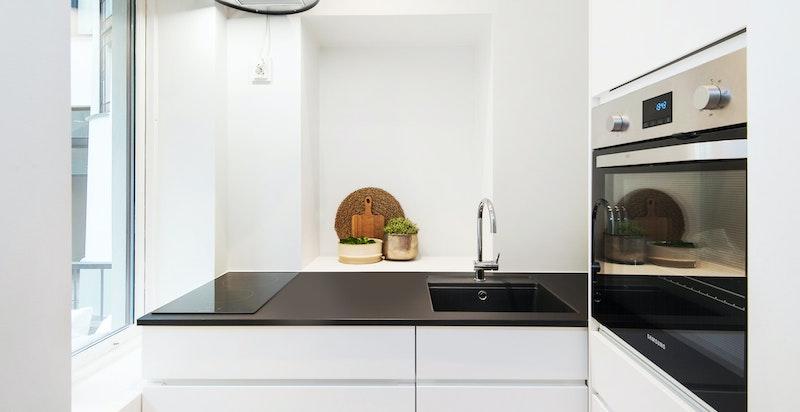 Kjøkkenet har integrerte hvitevarer som stekeovn og koketopp.