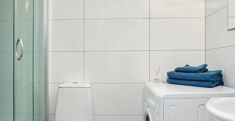 Badet inneholder servant, wc, vaskemaskin samt dusjkabinett.