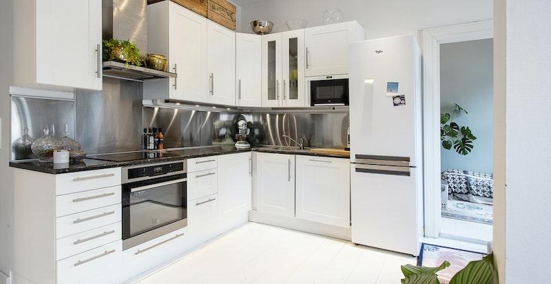 Kjøkkenet med hvit høyglans innredning, samt inntegrert komfyr og platetopp.