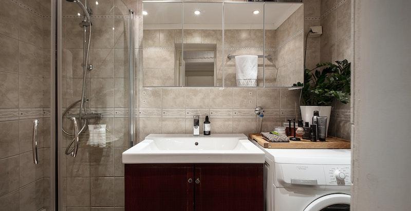 Flislagt bad oppvarmet med varmekabler i gulv. Inneholder dusjhjørne, servant og opplegg til vaskemaskin/tørketrommel.