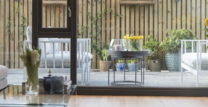 Om sommeren blir uteområdet en naturlig forlengelse av stuen takket være store glassvegger og skyvedører