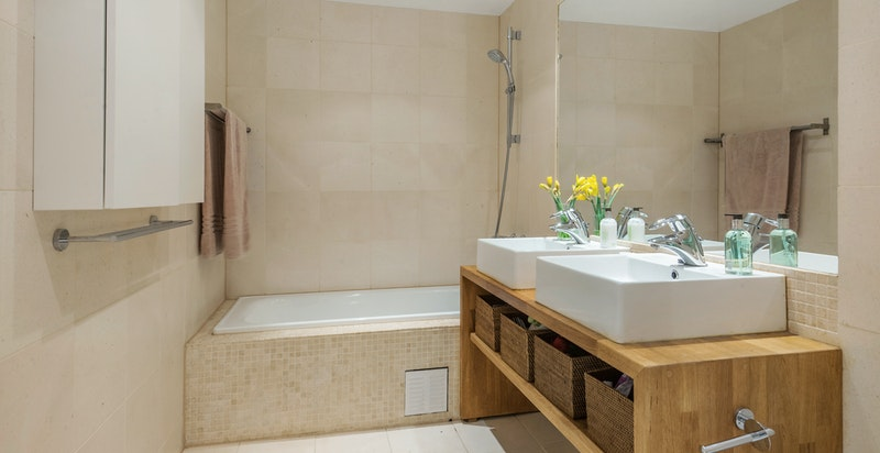 Pent hovedbad med italienske fliser, badekar, og eikeinnreding med to servanter