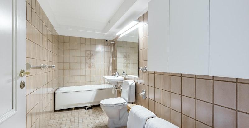 Badet er romslig og flislagt. Det er god plass til vaskemaskin og tørketrommel.