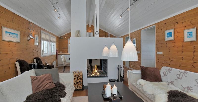 Hyggelig stue med mange vindusflater. Stuen og spiseplass/kjøkken er delt med stor peis med åpning begge veier