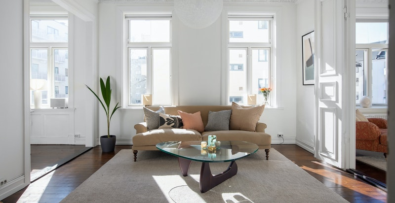 Lys og åpen stue med god takhøyde (3 m), store vindusflater og åpning til både spisestue/kjøkken og TV-stue/soverom