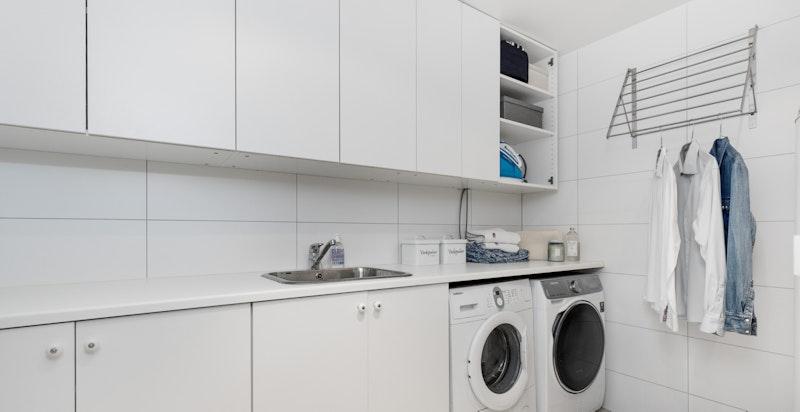 Praktisk og romslig vaskerom i kjeller med opplegg for vaskemaskin og tørketrommel