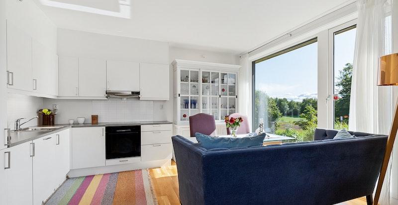 Romslig kjøkken med plass for stort spisebord. Store vindusflater gir mye lys. Romslig benkeplass og rikelig med lagringsplass på kjøkkenet.