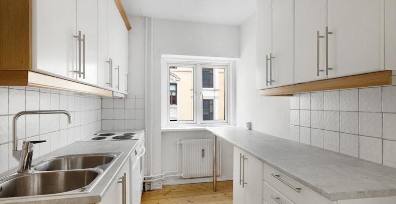 Romslig kjøkken med vindu i rommet og praktisk designet kjøkken med god benke- og skapplass.