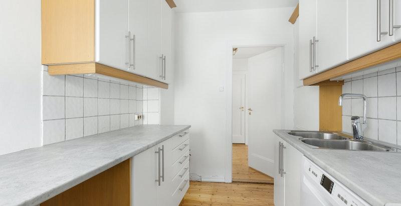 Kjøkkenet er utstyrt med rustfri oppvaskkum, ettgreps blandebatteri, oppvaskmaskin, komfyr og ventilator over koketopp.