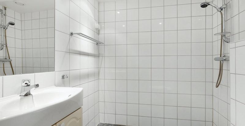 Pent og delikat flislagt bad rehabilitert i regi av selskapet i 2004. Badet har grå gulvfliser, hvite veggfliser, gulvvarme og downlightsbelysning.