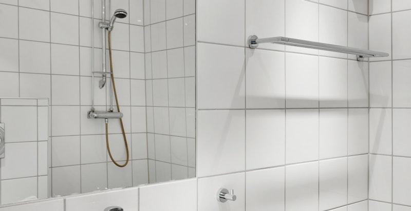Badet er utstyrt med servant i underskap med oppbevaringsplass, ettgreps blandebatteri, speil over servant, veggmontert dusj og veggplassert toalett.