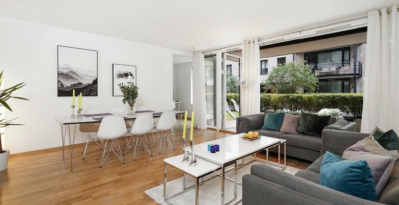 Romslig stue med plass for både spisebord og salong. Utgang terrasse.