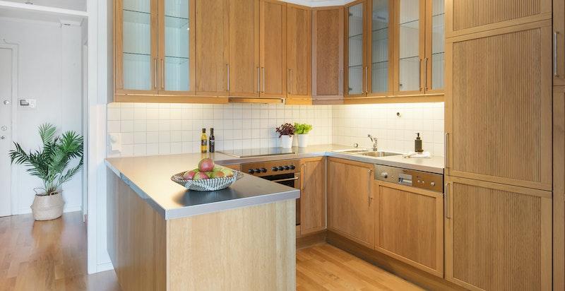Kjøkkenet er i egen kjøkkenkrok og har godt med benkeplass og skapplass.