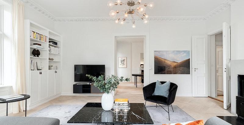 Stor og lys stue med peis, god takhøyde og flotte klassiske godt bevarte detaljer